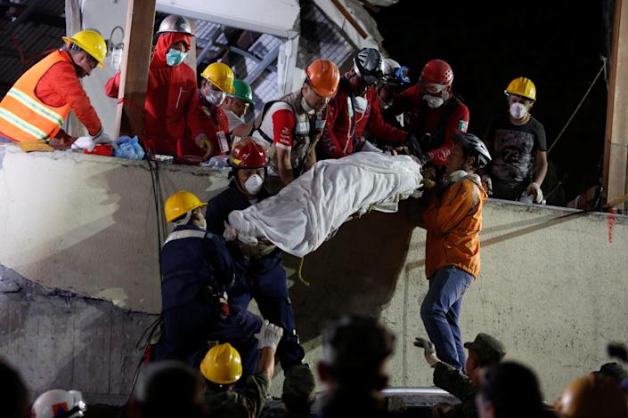 <p>Rescue workers remove a dead body after searching through rubble in a floodlit search for students at Enrique Rebsamen school in Mexico City, Mexico, Sept. 20, 2017. (Photo: Carlos Jasso/Reuters) </p>