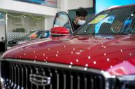 People look at a Geely vehicle at a car dealership in Shanghai