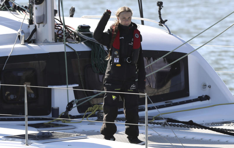 Climate activist Greta Thunberg waves as she arrives in Lisbon aboard the sailboat La Vagabonde Tuesday, Dec 3, 2019. Thunberg has arrived by catamaran in the port of Lisbon after a three-week voyage across the Atlantic Ocean from the United States. The Swedish teen sailed to the Portuguese capital before heading to neighboring Spain to attend the U.N. Climate Change Conference taking place in Madrid. (AP Photo/Pedro Rocha)