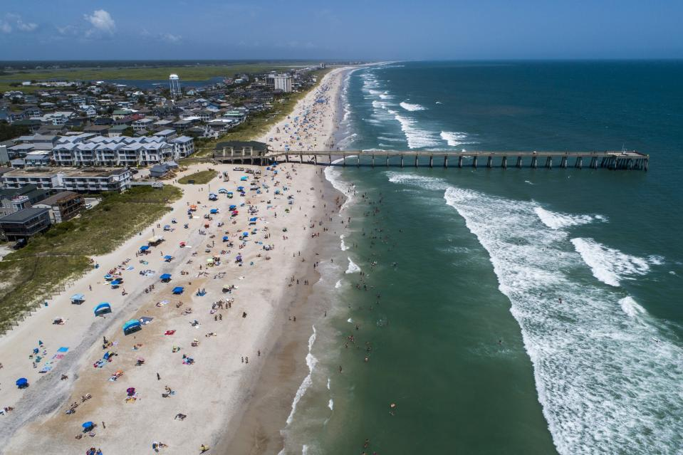 Beachgoers pack Wrightsville Beach, N.C., Sunday, Aug. 2, 2020 as Tropical Storm Isaias moves along the Southeast Coast. (Travis Long/The News & Observer via AP)
