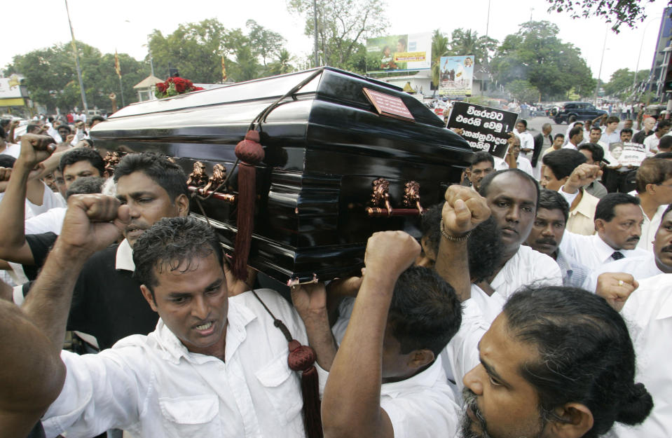 FILE - In this Monday, Jan. 12, 2009, file photo, Sri Lankans shout slogans against the government during the funeral procession of the Sunday Leader newspaper editor Lasantha Wickrematunge, in Colombo, Sri Lanka. The daughter of the slain journalist filed a complaint Friday, Jan. 8, 2021, with the United Nations Human Rights Committee over alleged government involvement in her father's death 12 years ago. The San Francisco-based Center for Justice and Accountability filed the complaint on behalf of Ahimsa Wickrematunge, the daughter of Lasantha, who was allegedly killed by a military-linked hit squad while driving to work on Jan. 8, 2009. (AP Photo/Gemunu Amarasinghe, File)