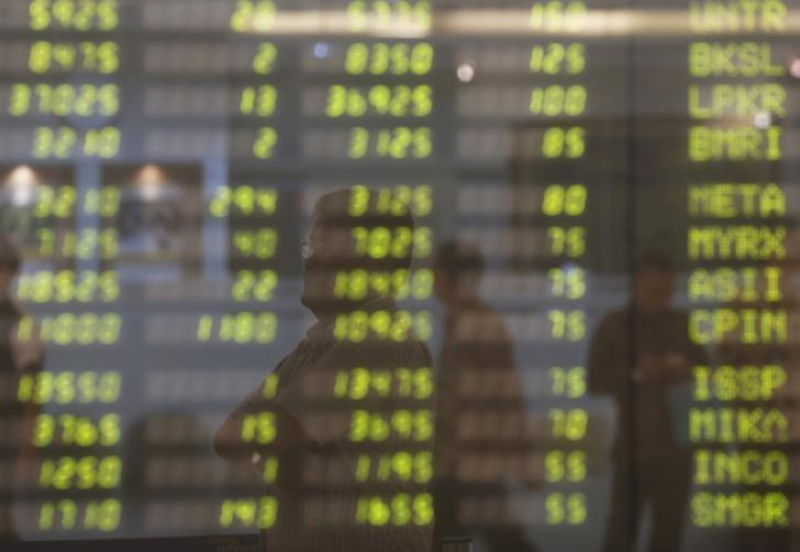 A man stands near an electronic board showing the stock market index at the Bank Mandiri Sekuritas trading floor in Jakarta November 25, 2015. REUTERS/Beawiharta
