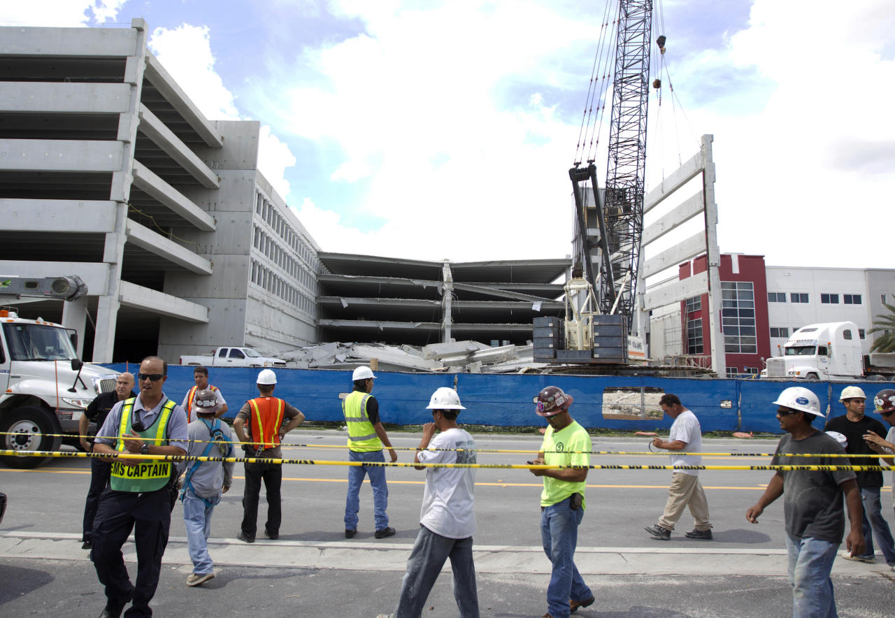 Construction workers gather near the rubble after a section of a parking garage under construction at a Miami-Dade College campus collapsed, Wednesday, Oct. 10, 2012 in Doral, Fla., killing one worker and trapping at least two others in the rubble, officials said. (AP Photo/J Pat Carter)