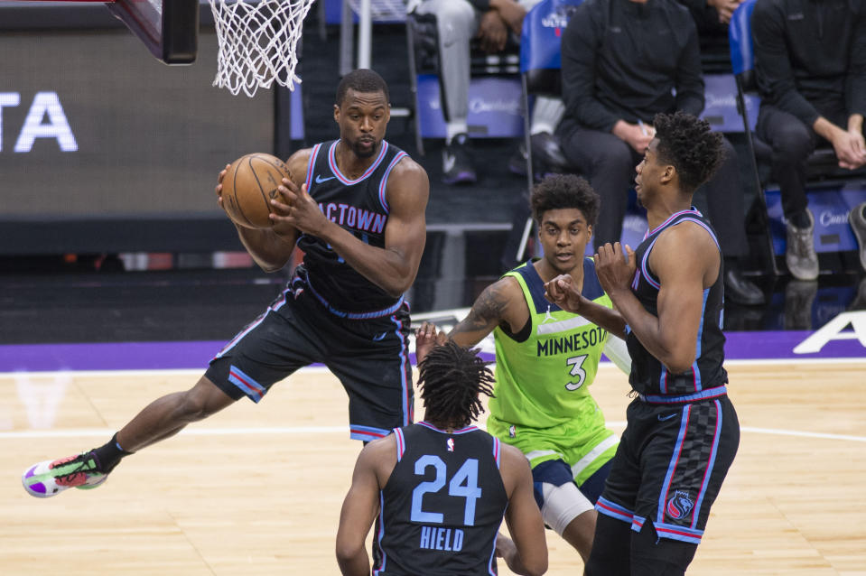 Sacramento Kings forward Harrison Barnes (40) picks up a defensive next to Minnesota Timberwolves forward Jaden McDaniels (3) and Kings guard Buddy Hield (24) and center Hassan Whiteside (20) during the first quarter of an NBA basketball game in Sacramento, Calif., Wednesday, April 21, 2021. (AP Photo/Hector Amezcua)