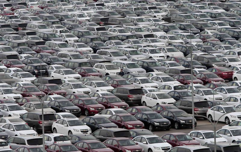 An employee yawns as he walks among General Motors' new Chinese-made cars at a parking lot in Shenyang, Liaoning province