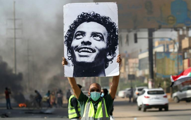 A mask-clad man holds up a picture of a Abdulsalam Kisha, a Sudanese protester who was killed in the raid