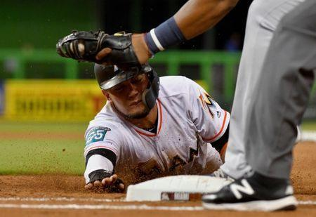 Jul 11, 2018; Miami, FL, USA; Miami Marlins shortstop Miguel Rojas (19) dives back to first base as Milwaukee Brewers first baseman Jesus Aguilar (24) is late with the tag in the fourth inning at Marlins Park. Mandatory Credit: Steve Mitchell-USA TODAY Sports