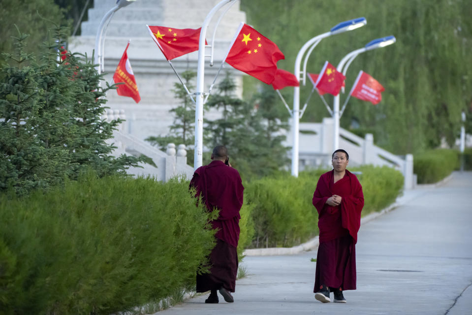 Monks walk along a sidewalk path lined with Chinese flags at the Tibetan Buddhist College near Lhasa in western China's Tibet Autonomous Region, Monday, May 31, 2021, as seen during a government organized visit for foreign journalists. High-pressure tactics employed by China's ruling Communist Party appear to be finding success in separating Tibetans from their traditional Buddhist culture and the influence of the Dalai Lama. (AP Photo/Mark Schiefelbein)