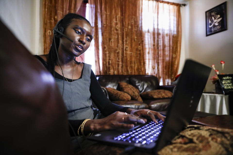 Maryama Diaw, a contact tracer with New York City's Health + Hospitals battling the coronavirus pandemic, sets up her remote calling system at her home before reaching out to potential patients Wednesday, Aug. 5, 2020, in New York. The city has hired more than 3,000 tracers and the city says it's now meeting its goal of reaching about 90% of all newly diagnosed people and completing interviews with 75%. (AP Photo/John Minchillo)