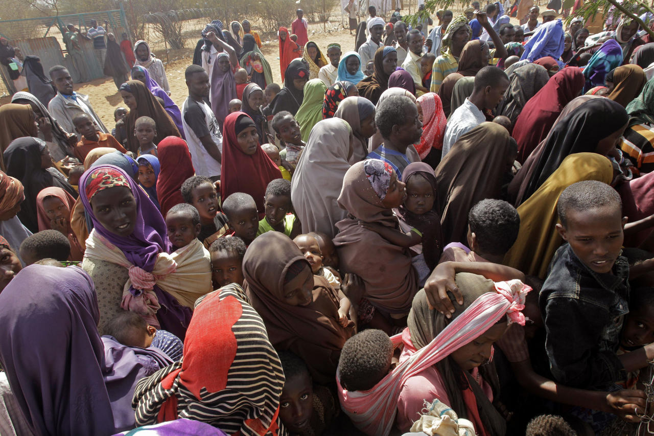 People wait outside a food distribution center to be registered as refugees in Dadaab, Kenya, Monday, Aug 1, 2011. Dadaab, a camp designed for 90,000 people now houses around 440,000 refugees. Almost all are from war-ravaged Somalia, with some having been here for more than 20 years, when the country first collapsed into anarchy. (AP Photo/Schalk van Zuydam)