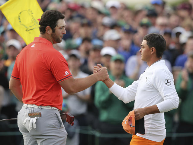 Ricky Fowler, right, greets Jon Rahm finishing his round at 14-under par, one stroke off from winner Patrick Reed, on the 18th green at the Masters golf tournament Sunday, April 8, 2018, in Augusta, Ga. (Curtis Compton/Atlanta Journal-Constitution via AP)
