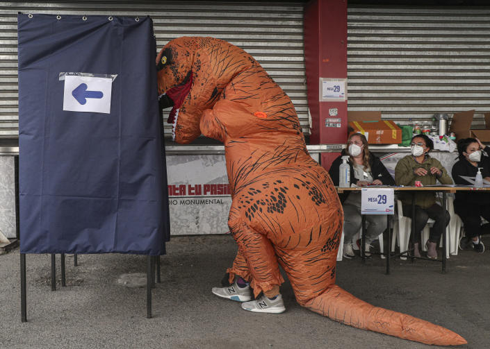 A person in a dinosaur suit votes during the second day of the Constitutional Convention election to select assembly members that will draft a new constitution, in Santiago, Chile, Sunday, May 16, 2021. (AP Photo/Esteban Felix)