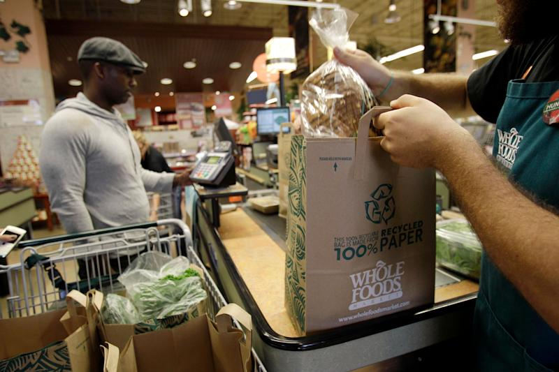 FILE - In this Nov. 3, 2010 photo, a worker bags a customer's items at Whole Foods, in Coral Gables, Fla. Whole Foods Market Inc. releases quarterly financial earnings Wednesday, Feb. 9, 2011, after the market close.(AP Photo/Lynne Sladky, file)