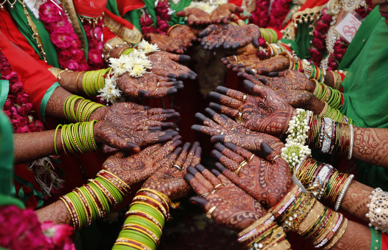 In this Sunday, Nov. 4, 2018, file photo, Indian Muslim brides display henna designs on their hands during a mass marriage in Ahmadabad, India. Thirty five couples were married off in a mass marriage ceremony. Mass weddings in India are organized by social organizations primarily to help the economically backward families who cannot afford the high ceremony costs as well as the customary dowry and expensive gifts that are still prevalent in many communities. (AP Photo/Ajit Solanki, File)