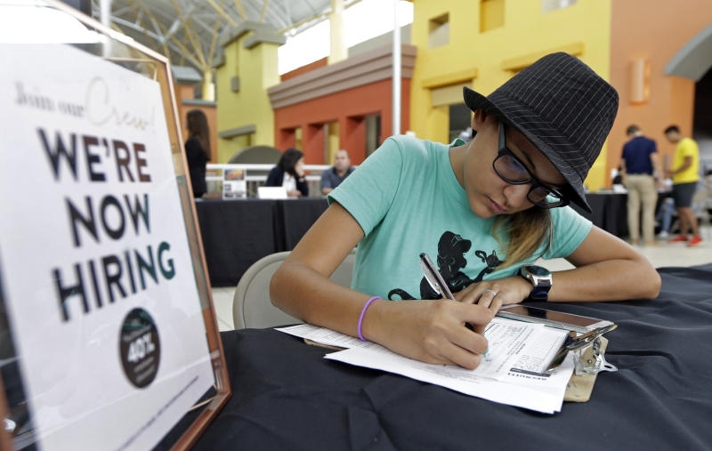 FILE - In this Oct. 4, 2017 file photo, job seeker Alejandra Bastidas fills out an application at a job fair in Sweetwater, Fla. U.S. workers' wages and benefits grew 2.6 percent last year, the fastest 12-month pace since the spring of 2015. The 12-month gain in wages and benefits came despite a slight slowdown at the end of last year with wages and benefits rising 0.6 percent in the fourth quarter, a tiny dip from a 0.7 percent gain in the third quarter. Still, the 12-month gain was an improvement from a 2.2 percent gain for the 12 months ending in December 2016. (AP Photo/Alan Diaz, File)