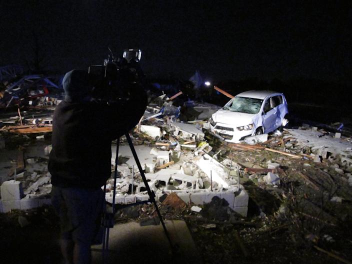 A news cameraman shoots video of the rubble of an auto parts store destroyed by a tornado in Washington, Ill., on Sunday, Nov. 17, 2013. Illinois State Police says everal people were inside at the time the tornado hit but all escaped uninjured. The tornado cut a path of destruction through Washington. (AP Photo/David Mercer)