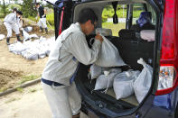 A city official loads sandbags into the car of an applicant in Iwaki, Fukushima prefecture, Monday, July 26, 2021 in preparation for a tropical storm heading toward northeastern Japan. Storm and high wave warnings were issued for Miyagi and Fukushima prefectures. (Kyodo News via AP)