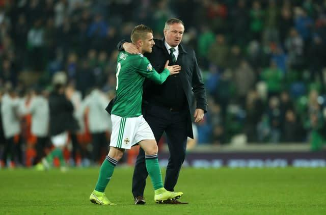 Steven Davis, who missed a penalty, and manager Michael O'Neill, who is stepping down to join Stoke, embrace after Northern Ireland's draw with Holland (Liam McBurney/PA)