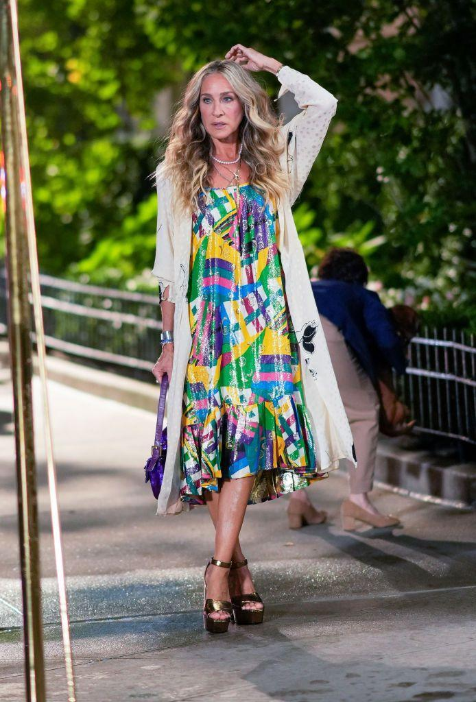 <p>Parker stepped out on the town in a colorful dress and white cardigan, paired with statement golden platform sandal heels.</p>