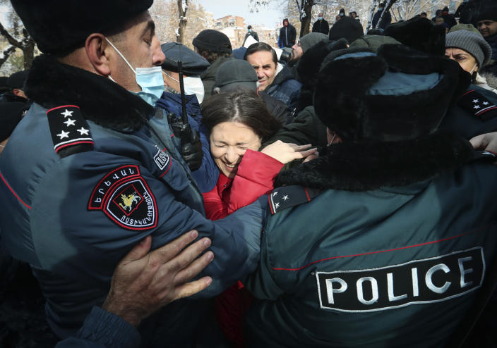 Demonstrators scuffle with Armenian police during a rally to pressure Armenian Prime Minister Nikol Pashinyan to resign over a peace deal with neighboring Azerbaijan on Republic Square in Yerevan, Armenia, Thursday, Dec. 24, 2020. Armenian opposition politicians and their supporters have been protesting for weeks, demanding the prime minister's resignation over his handling of the Nagorno-Karabakh conflict with Azerbaijan. (Vahram Baghdasaryan, Photolure via AP)