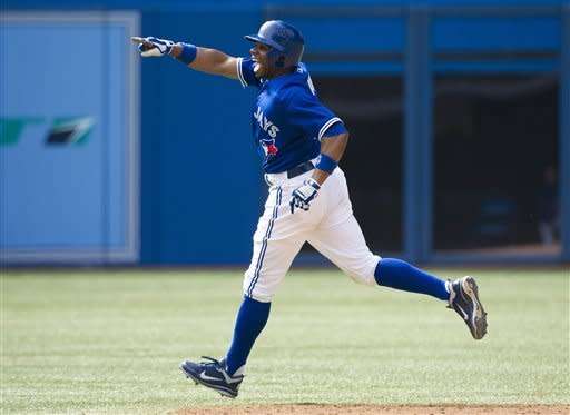 Toronto Blue Jays' Rajai Davis points to teammates after hitting the game-winning two-run home run against the Philadelphia Phillies during tenth-inning interleague baseball game action in Toronto, Saturday, June 16, 2012. (AP Photo/The Canadian Press, Nathan Denette)