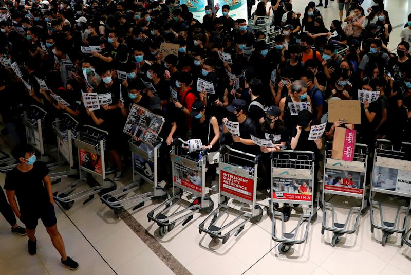 Anti-extradition bill protesters use trolleys to stop passengers from entering the security gates during a mass demonstration after a woman was shot in the eye, at the Hong Kong international airport, in Hong Kong China August 13, 2019. (Photo: Tyrone Siu/Reuters)