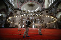 FILE - In this Tuesday, May 26, 2020, file photo, municipality workers disinfect the grounds of the historical Suleymaniye Mosque, in Istanbul, during the third day of Eid el-Fitr and the last day of a four-day curfew due to the coronavirus outbreak. When Turkey changed the way it reports daily COVID-19 infections, it confirmed what medical groups and opposition parties have long suspected — that the country is faced with an alarming surge of cases that is fast exhausting the Turkish health system. The official daily COVID-19 deaths have also steadily risen to record numbers in a reversal of fortune for the country that had been praised for managing to keep fatalities low. With the new data, the country jumped from being one of the least-affected countries in Europe to one of the worst-hit. (AP Photo/Emrah Gurel, File)