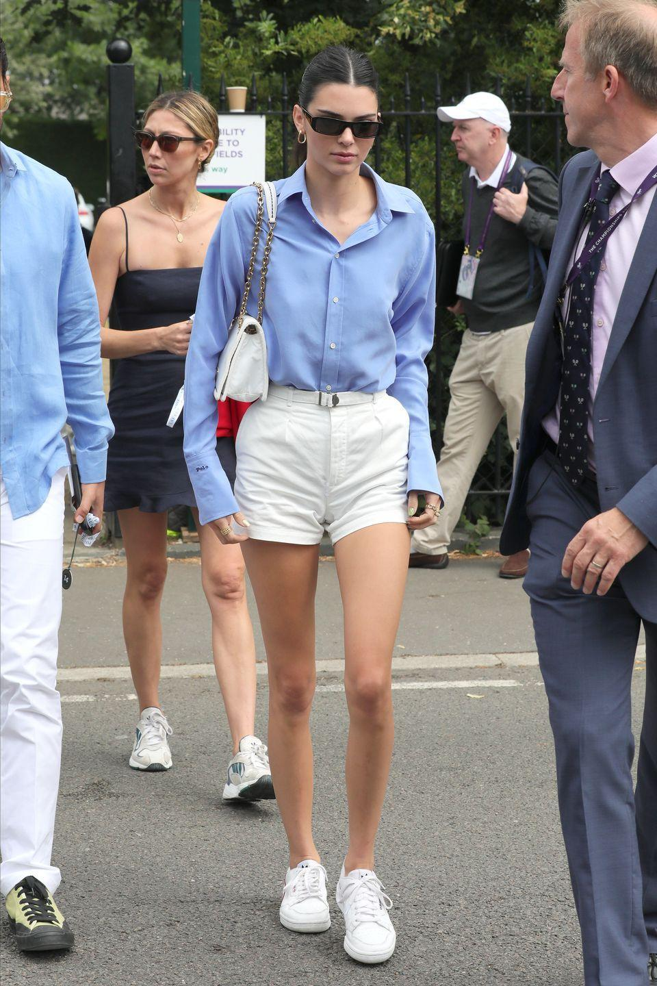 <p>The model kept it cute in a Ralph Lauren Polo long-sleeve blue shirt and white waist high shorts for her visit to SW19.</p>