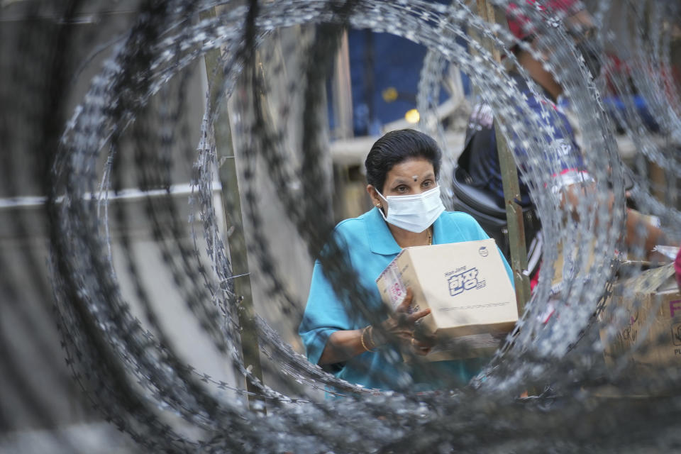 A resident wearing a face mask collects her package behind barbed wire outside the Pangsapuri Permai housing which is placed under the enhanced movement control order (EMCO) due to the drastic increase in the number of Covid-19 cases recorded over the past 10 days in Cheras, outside Kuala Lumpur, Malaysia, Friday, May 28, 2021. Malaysia's latest coronavirus surge has been taking a turn for the worse as surging numbers and deaths have caused alarm among health officials, while cemeteries in the capital are dealing with an increasing number of deaths. (AP Photo/Vincent Thian)