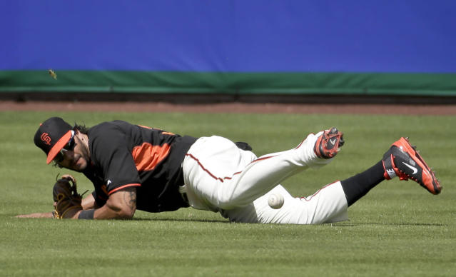 San Francisco Giants left fielder Michael Morse can't get a glove on a double by Colorado Rockies Paul Janish during the second inning of a spring exhibition baseball game in Scottsdale, Wednesday, March 26, 2014. (AP Photo/Chris Carlson)