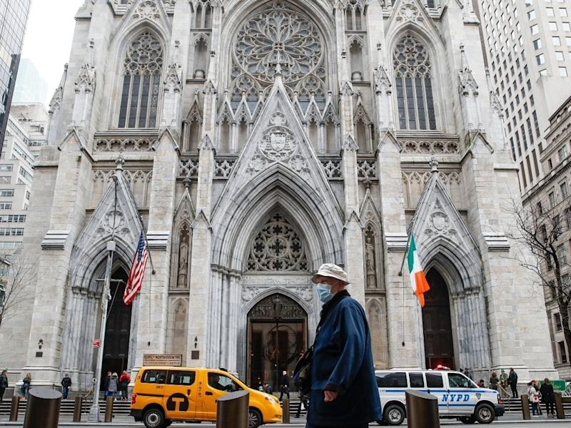 A pedestrian wearing a protective mask walks by St. Patrick's Cathedral in New York City.