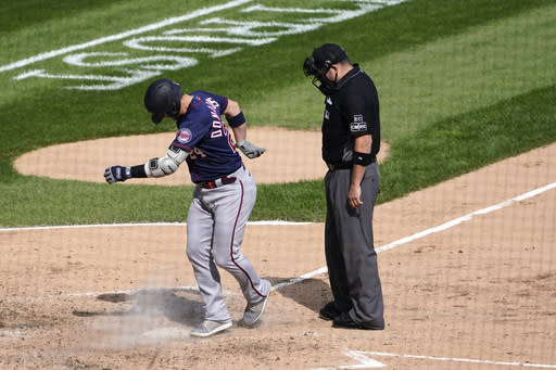 Minnesota Twins' Josh Donaldson kicks dirt on home plate after his home run prompting umpire Dan Bellino to eject him from the game during the sixth inning of a baseball game against the Chicago White Sox Thursday, Sept. 17, 2020, in Chicago. (AP Photo/Charles Rex Arbogast)