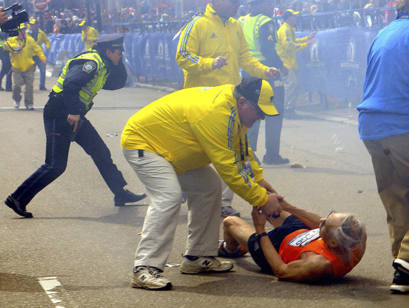 In this Monday, April 15, 2013 photo, a race official assists Bill Iffrig, 78, of Lake Stevens, Wash., as Iffrig lies on the ground after the first explosion, as police officers react to a second explosion at the finish line of the Boston Marathon in Boston, Monday, April 15, 2013.  Iffrig, of Lake Stevens, Wash., was running his third Boston Marathon and near the finish line when he was knocked down by one of two bomb blasts. (AP Photo/MetroWest Daily News, Ken McGagh)  MANDATORY CREDIT