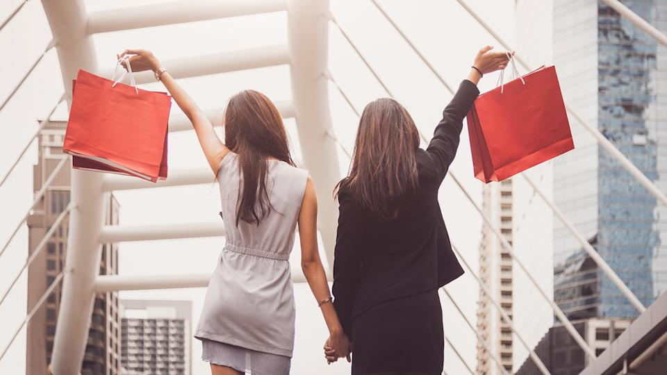 Shopaholic lifestyle friendship women holding shopping bag in shopping mall center.