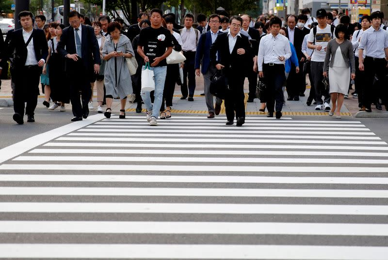 FILE PHOTO: Pedestrians make their way in a business district in Tokyo