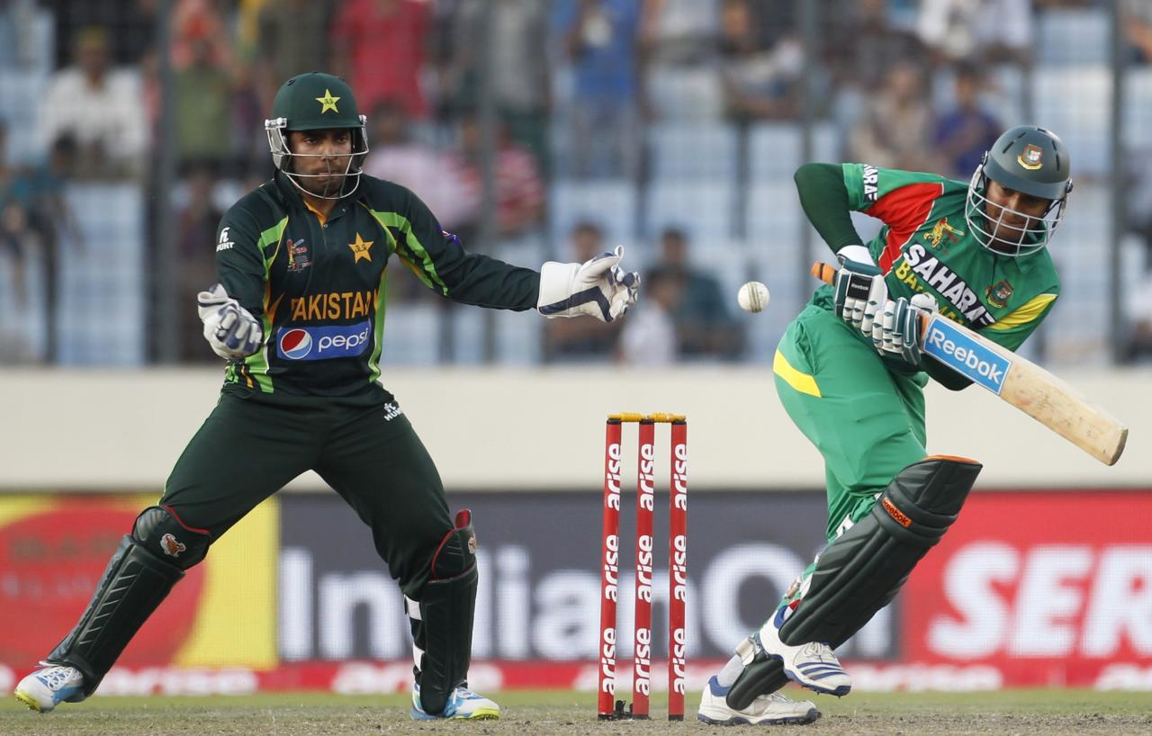 Bangladesh's Shakib Al Hasan (R) plays a ball as Pakistan's wicketkeeper Umar Akmal tries to catch during their one-day international (ODI) cricket match in Asia Cup 2014 in Dhaka March 4, 2014. REUTERS/Andrew Biraj (BANGLADESH - Tags: SPORT CRICKET)