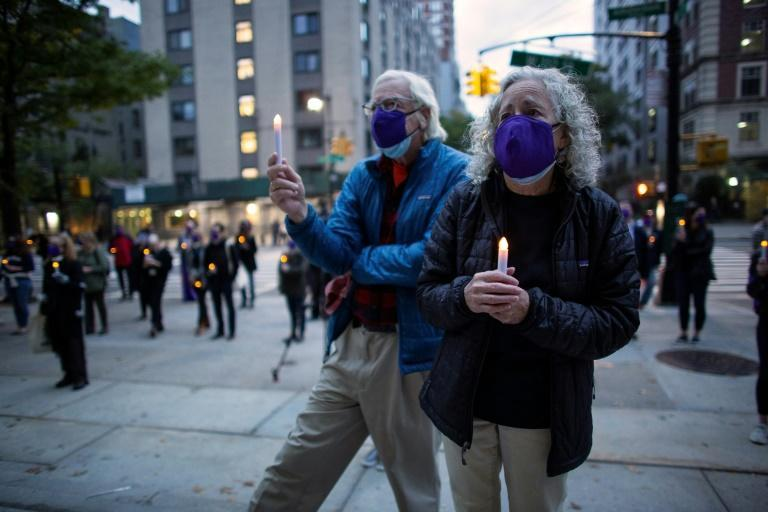 People attend a candlelight vigil in tribute to all the lives affected by the novel coronavirus, outside the Cathedral of St John the Divine in New York City on on October 19, 2020