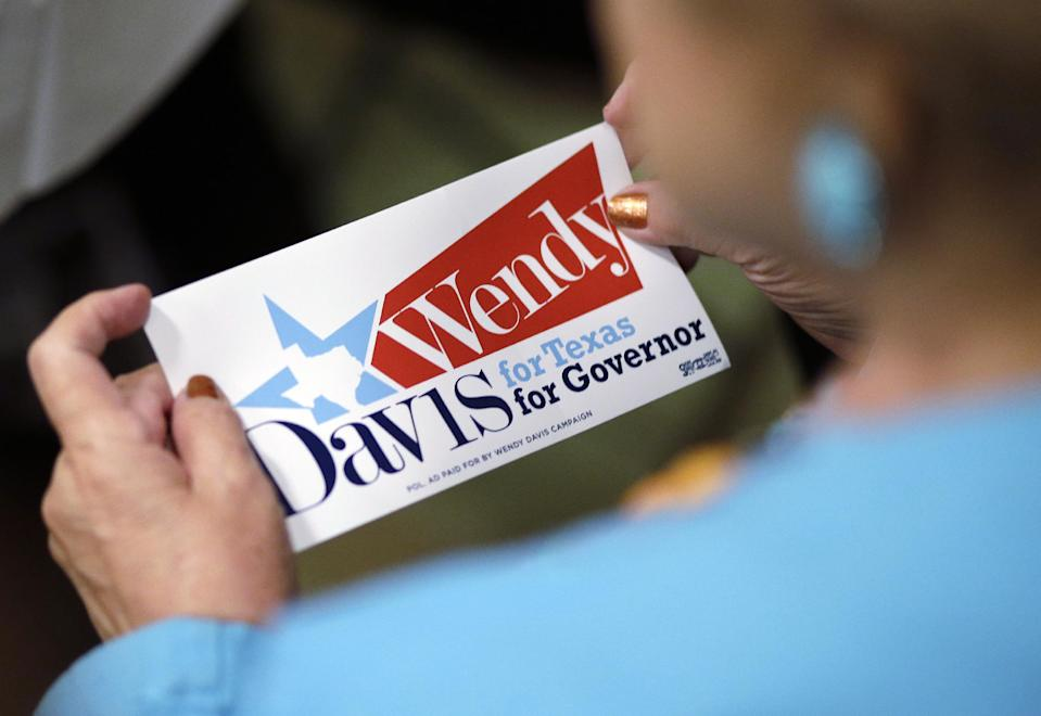 """A supporter holds a """"Wendy Davis for Governor"""" sticker during an announcement watch party for State Sen. Wendy Davis, Thursday, Oct. 3, 2013, in San Antonio. Davis formally announced her campaign for governor, becoming the first Democrat to make an official bid for a statewide office. (AP Photo/Eric Gay)"""