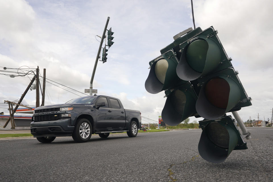 Traffic passes by a traffic light hanging from a cable after Hurricane Ida moved through Monday, Aug. 30, 2021, in LaPlace, La. (AP Photo/Steve Helber)