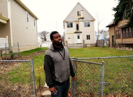 Brandon who was hospitalized for severe lead poisoning from paint chips when he was one, almost 20 years ago stands in front of the house where he lived in Milwaukee, Wisconsin, U.S. November 30, 2016. REUTERS/Darren Hauck