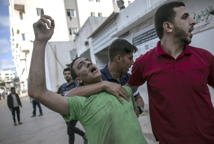 A Palestinian man reacts to the death of his father who was killed by an Israeli airstrike that destroyed the upper floors of a commercial building and caused damage to the nearby Health Ministry and prime health care clinic, in Gaza City, Monday, May 17, 2021. (AP Photo/Khalil Hamra)