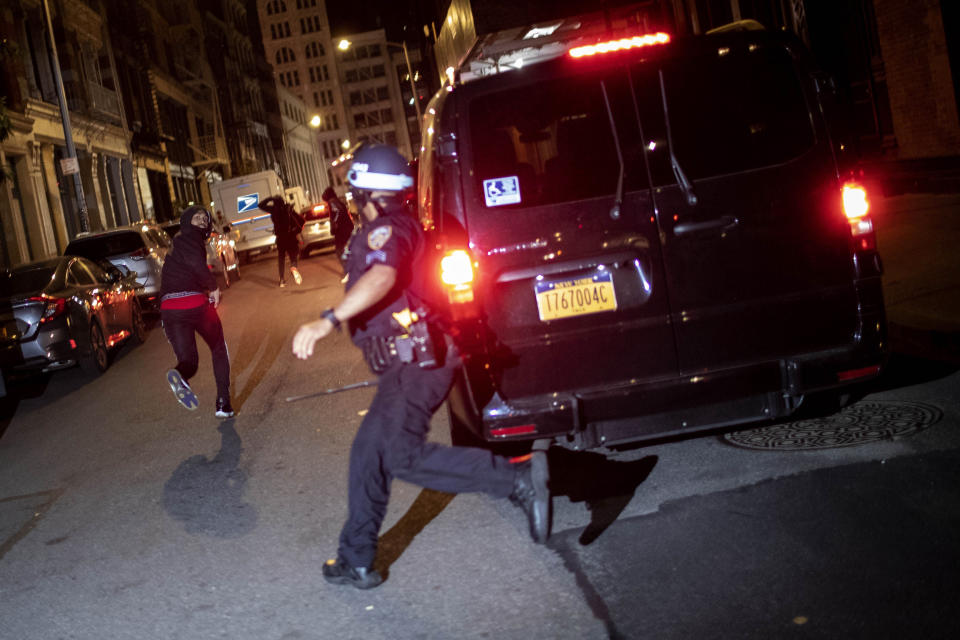 FILE - In this June 1, 2020, file photo, a protester runs as he is chased by police in New York. A grim video of a Chicago police officer fatally shooting a 13-year-old boy is once again shining a light on the policies that govern foot chases. (AP Photo/Wong Maye-E, File)