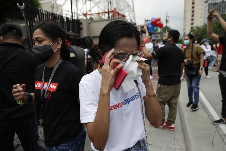 A supporter wipes her tears after hearing the results of the voting at the House of Representative for the franchise renewal of ABS-CBN at the company headquarters of ABS-CBN in Quezon City, Philippines, Friday, July 10, 2020. Philippine lawmakers voted Friday to reject the license renewal of the country's largest TV network, shutting down a major news provider that had been repeatedly threatened by the president over its critical coverage. (AP Photo/Aaron Favila)
