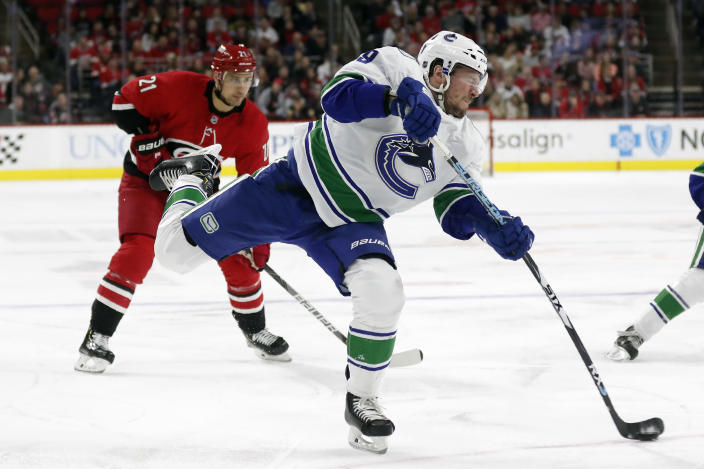 Vancouver Canucks center J.T. Miller (9) shoots on goal while Carolina Hurricanes right wing Nino Niederreiter (21), of Switzerland, looks on during the first period of an NHL hockey game in Raleigh, N.C., Sunday, Feb. 2, 2020. (AP Photo/Gerry Broome)