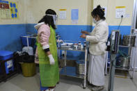 Shimray Wungreichon, 43, right, prepares to administer a shot to a patient at the District Hospital where she is the single nurse on overnight duty at the emergency ward, in Ukhrul, in the northeastern Indian state of Manipur, Friday, Jan. 15, 2021. Wungreichon was among the first of many Indian health workers to be vaccinated on Saturday, opening a new chapter in the battle against the pandemic in the world's second hardest-hit country, which has been scarred profoundly by a virus that has killed more than 152,000 of its people. (AP Photo/Yirmiyan Arthur)