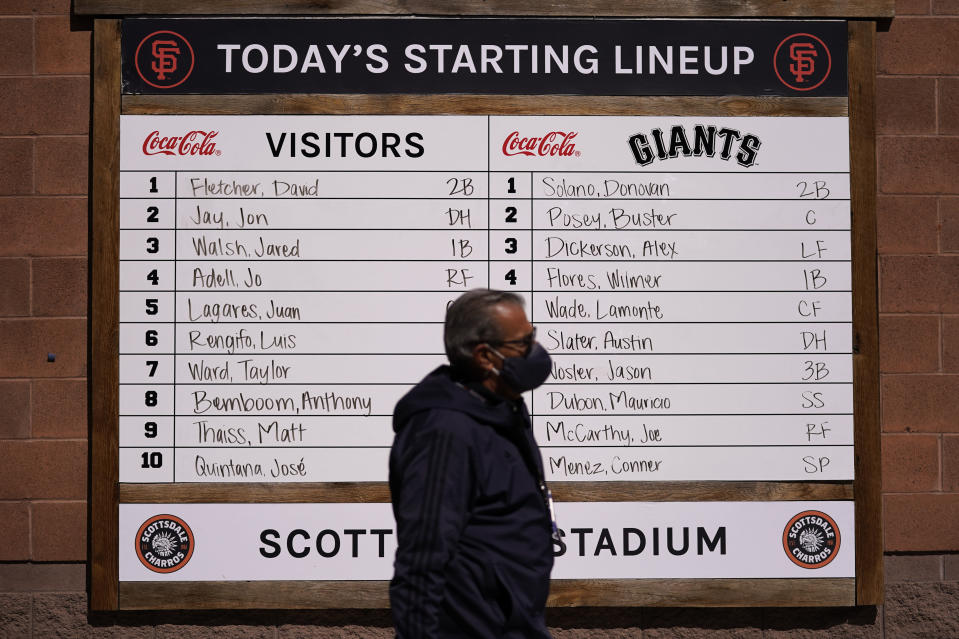 A man with a face mask walks past a lineup board before a spring baseball between the San Francisco Giants and the Los Angeles Angels in Scottsdale , Ariz., Sunday, Feb. 28, 2021. (AP Photo/Jae C. Hong)