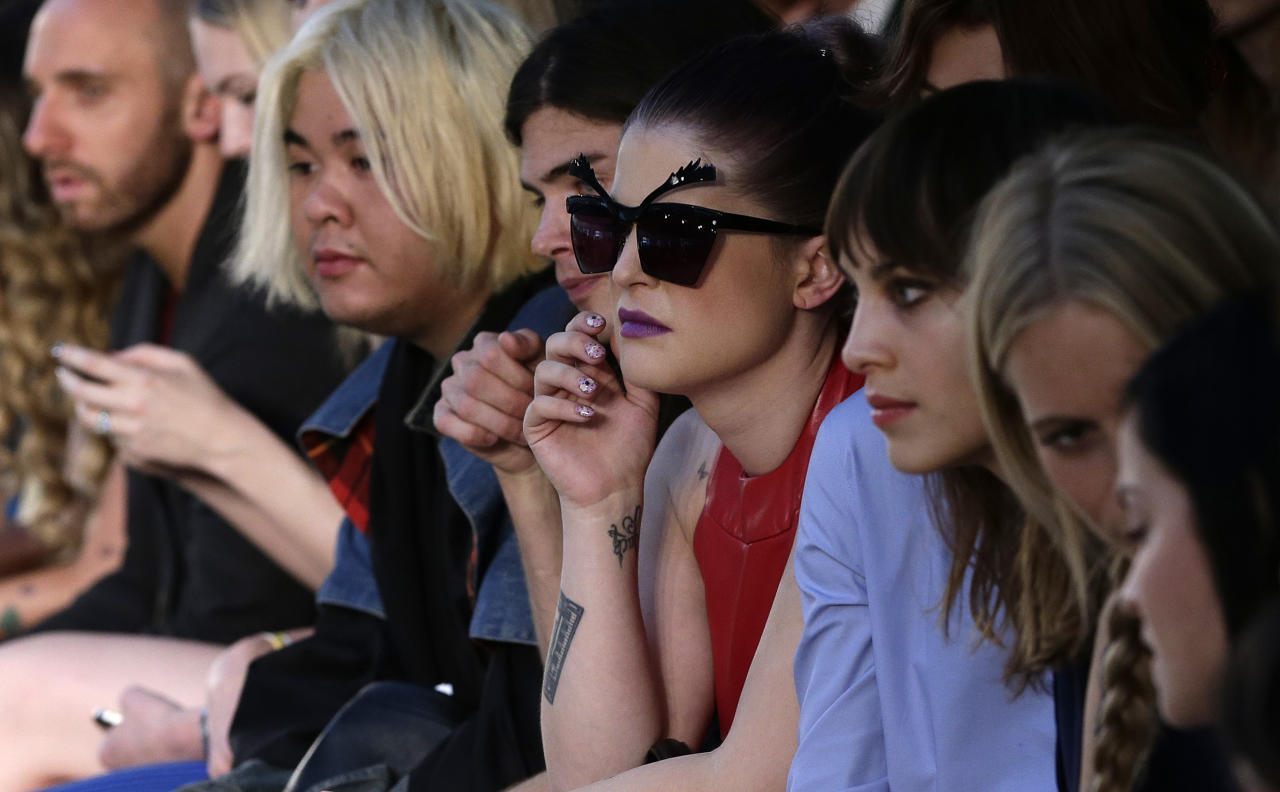British TV personalitiy Kelly Osbourne, in sun glasses watches the House of Holland Spring/Summer 2013 presentation at London Fashion Week in London, Saturday, Sept. 15, 2012. (AP Photo/Alastair Grant)