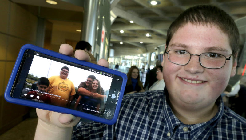 Sixteen-year-old Jason Alexander shows a photo of himself, second from left, taken four months ago when he left for a weight-loss boarding school, Friday, Dec. 21, 2012, at the Kansas City International Airport in Kansas City, Mo. Alexander, nearly 100 pounds lighter, was among 14 students from the Independence, Mo., school district to attend the program, losing 756 pounds among themselves. (AP Photo/Charlie Riedel)