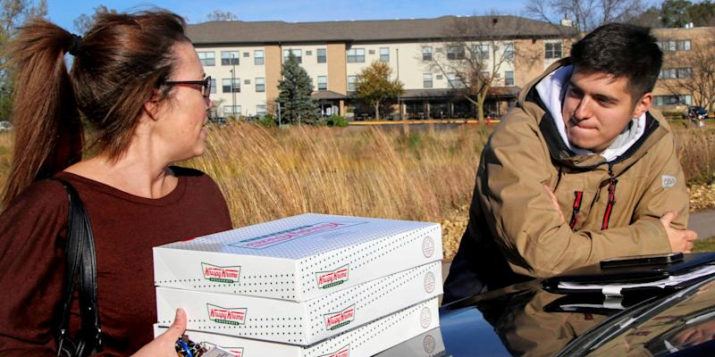 In this Saturday, Oct. 26, 2019 photo, Catherine Newton, left, buys three boxes of Krispy Kreme doughnuts from Jayson Gonzalez in Little Canada, Minn. Gonzalez, a Minnesota college student, says Krispy Kreme has told him to stop making doughnut runs to Iowa. Gonzalez told the Pioneer Press he was told his sales created a liability for the North Carolina-based company. (Deanna Weniger/Pioneer Press via AP)