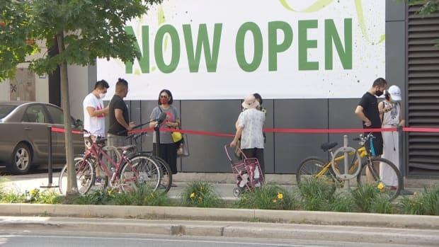 People wait in a line to shop at T&T Supermarket at its new downtown Toronto location. (CBC - image credit)